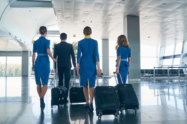 Quatre jeunes hôtesses de l'air tirant leurs valises trolley le long du terminal de l'aéroport