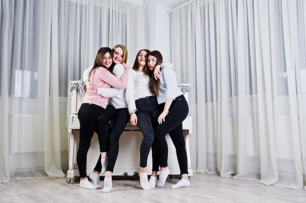 Quatre jolies amies filles portent des chandails chauds et un pantalon noir contre un vieux piano avec une décoration de noël dans la salle blanche.