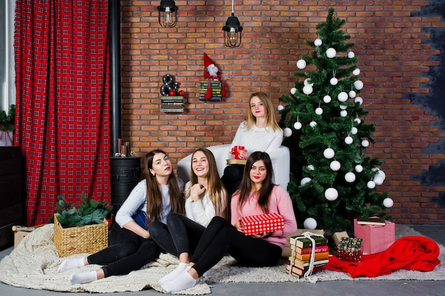 Quatre jolies amies filles portent des chandails chauds, des pantalons noirs et des chapeaux de père noël contre des arbres avec une décoration de noël
