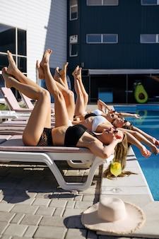 Quatre jolies femmes en maillot de bain bronzent sur des transats au bord de la piscine du complexe. de belles filles se détendent au bord de la piscine en journée ensoleillée, vacances d'été de copines séduisantes