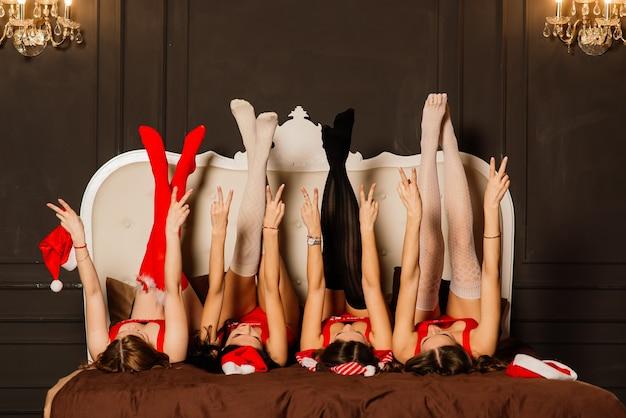 Quatre jolies jeunes femmes aux cheveux bouclés et lingerie de noël rouge. fond de nouvel an.