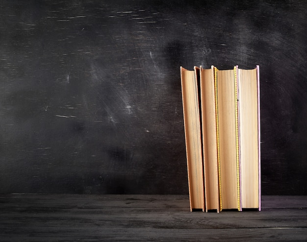 Quatre livres fermés avec des feuilles jaunes sur un tableau noir