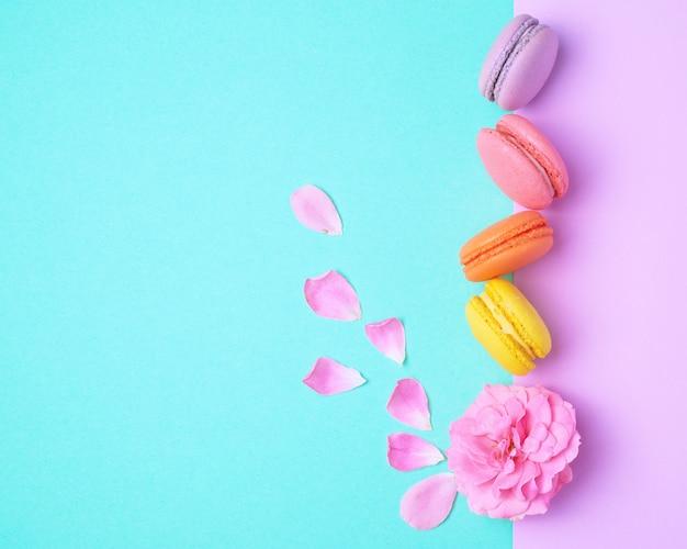Quatre macarons multicolores avec de la crème et un bouton de rose