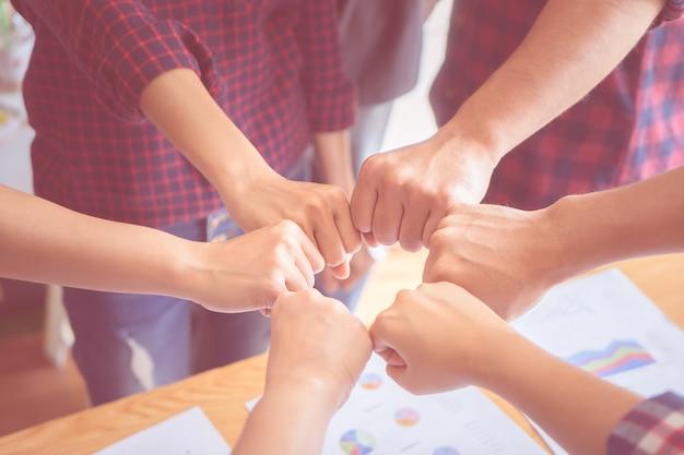 Quatre mains ensemble en réunion d'affaires pour le concept d'équipe