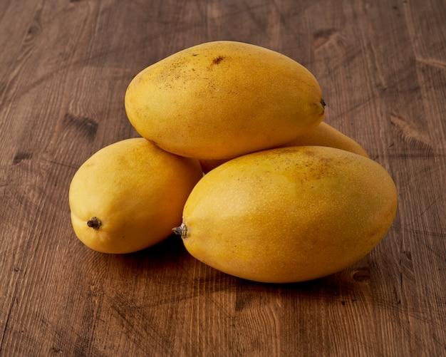 Quatre mangues aux fruits entiers sur table en bois. gros fruits jaunes mûrs lumineux juteux sur fond sombre