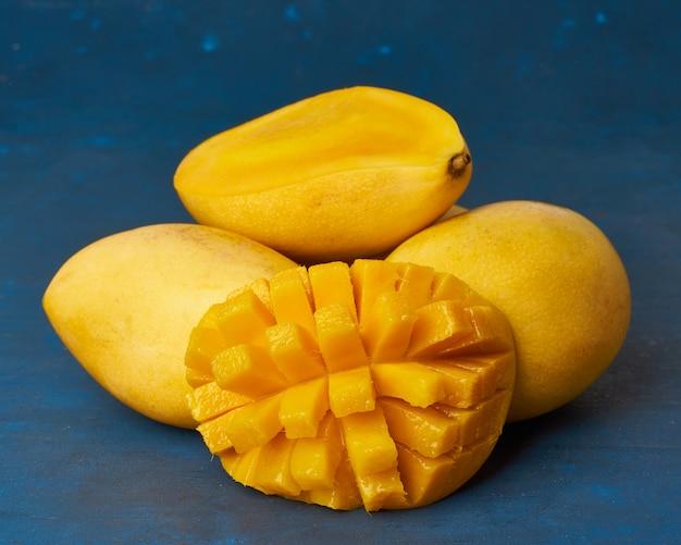 Quatre mangues entières sur une table bleu foncé et coupées en tranches. gros fruits jaunes mûrs juteux