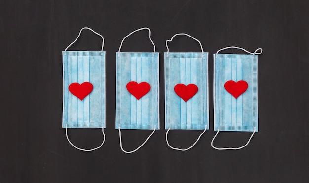 Quatre masques médicaux sur tableau noir
