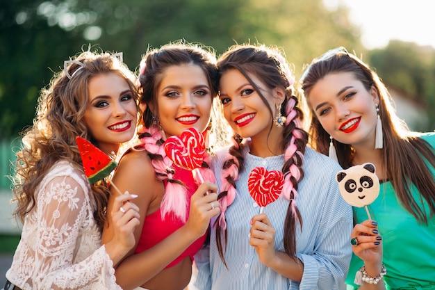 Quatre meilleures copines posant avec des bougies sur bâton et souriant.