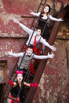 Quatre mimes debout dans les escaliers sur un mur rouge.