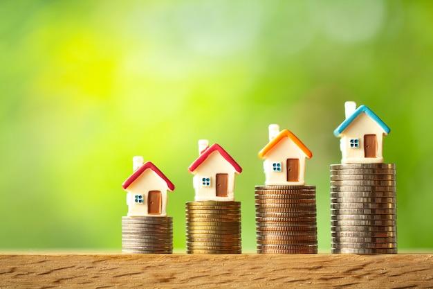 Quatre modèles de maison miniatures sur des piles de pièces de monnaie sur fond de verdure floue