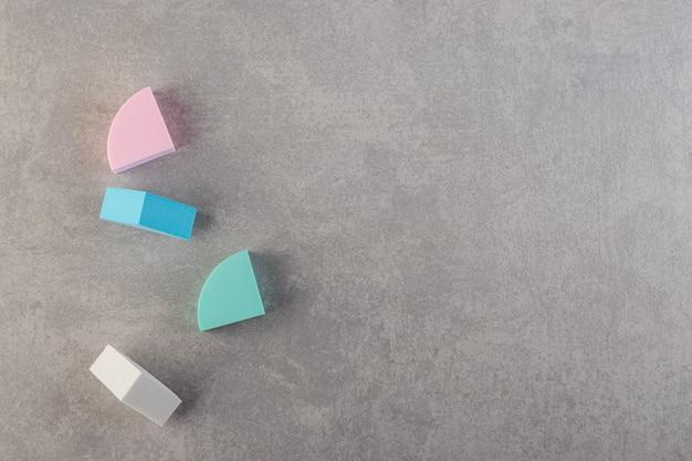 Quatre morceaux d'éponges douces colorées sur table en pierre.