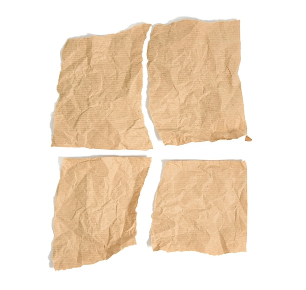 Quatre morceaux de papier kraft brun déchiré isolé sur fond blanc, vue du dessus