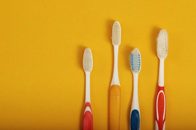 Quatre nouvelles et anciennes brosses à dents alignées sur un fond jaune.