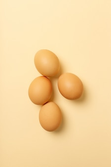 Quatre œufs isolés sur une surface jaune