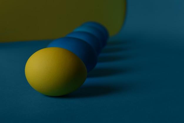 Quatre oeufs de pâques peints en bleu et un en jaune se trouvent en diagonale sur un fond bleu et jaune