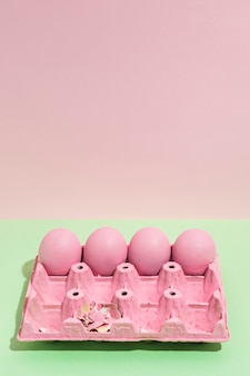Quatre oeufs de pâques roses dans un grand rack sur une table verte