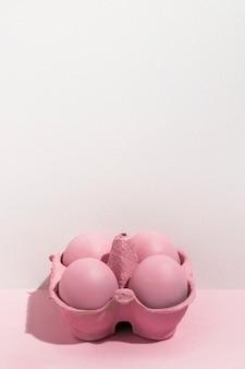 Quatre oeufs de pâques roses dans un petit rack sur la table
