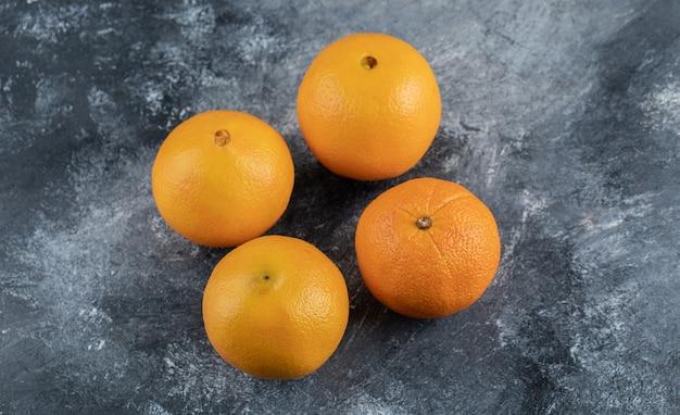 Quatre oranges savoureuses sur table en marbre.