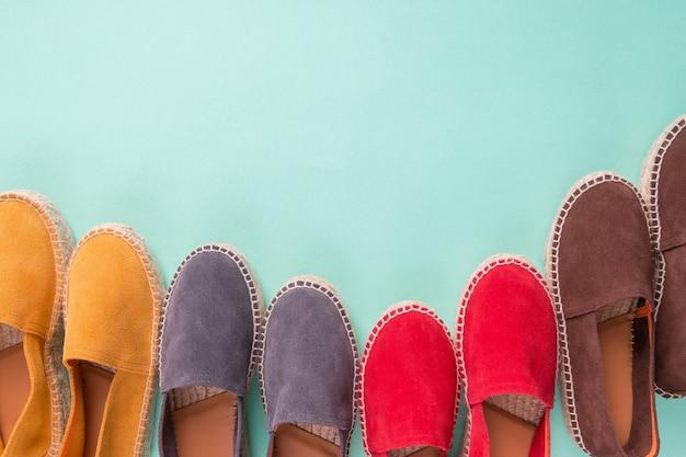 Quatre paires d'espadrilles sur fond de couleur menthe.