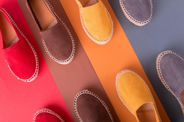 Quatre paires d'espadrilles sur fond multicolore. vue de dessus.