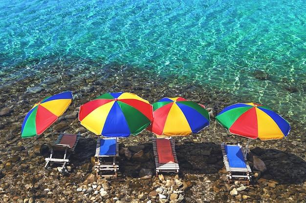 Quatre parasols et transats dans l'eau sur la plage de galets