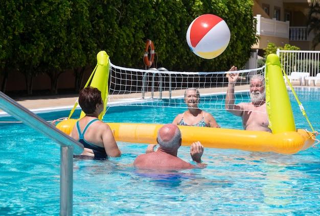 Quatre personnes âgées heureuses jouant au volley-ball dans la piscine avec filet gonflable et ballon profitant de l'été