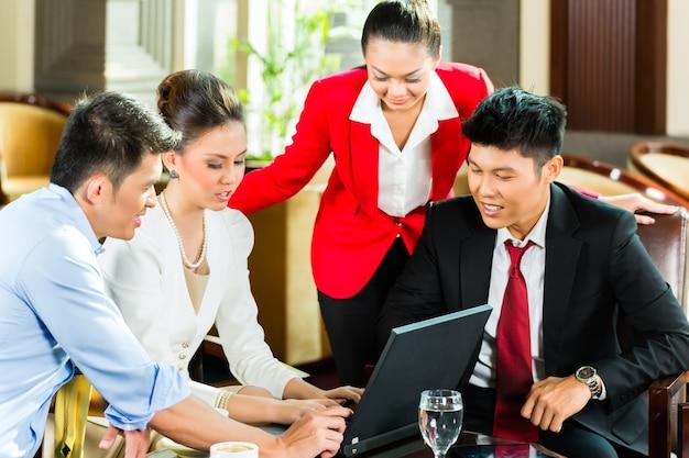 Quatre personnes de bureau chinois asiatiques ou hommes d'affaires et femmes d'affaires ayant une réunion d'affaires dans le hall d'un hôtel discutant de documents sur une tablette tout en buvant du café