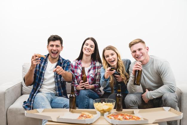 Les quatre personnes heureuses regardent la télévision avec une pizza et une bière sur fond blanc