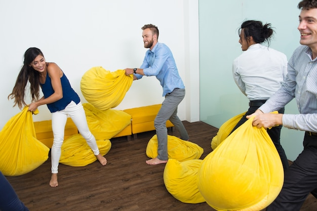 Quatre personnes ludiques se battant avec des oreillers