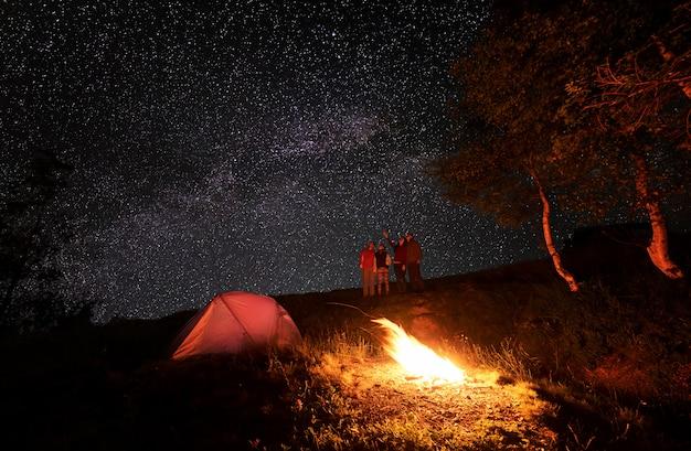Quatre personnes profitent du ciel insolite parsemé d'étoiles brillantes pendant le camping de nuit. une fille montre le reste du groupe sur la voie lactée. au premier plan, un feu brûle près de la tente et des arbres.
