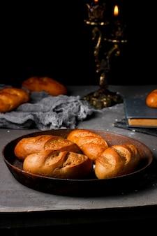 Quatre petites baguettes françaises placées sur une casserole en fer