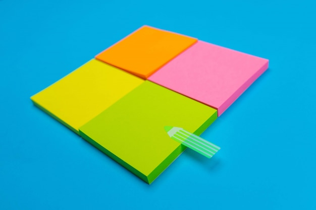 Quatre petites séries d'autocollants jaunes, oranges, roses, verts pliés dans un carré sur un bleu, dont l'un porte un autocollant vert en forme de bande. fermer. place pour les notes.