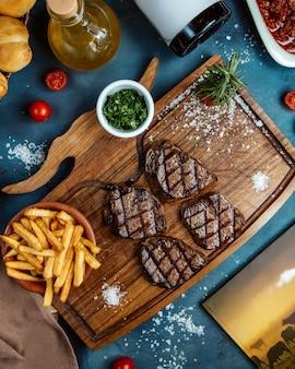 Quatre petits morceaux de steak servis avec des frites et des herbes en dés