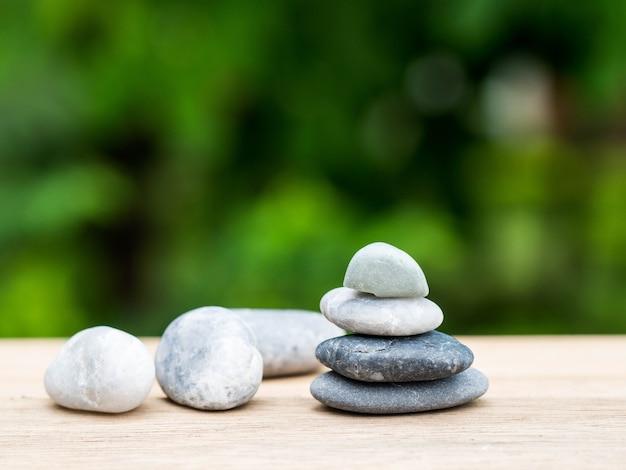 Quatre pierres empilées placées sur une planche de bois.