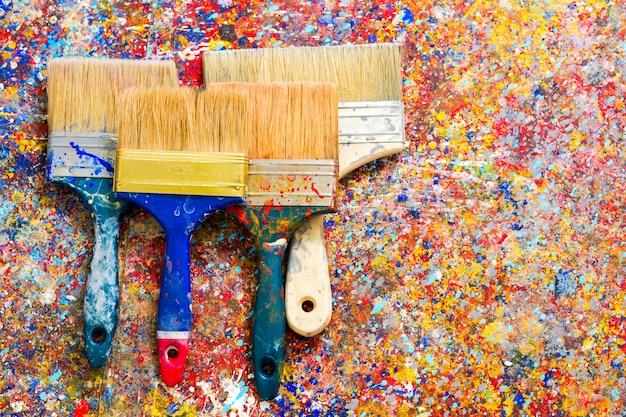 Quatre pinceaux sur les taches de peinture
