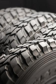 Quatre pneus tout-terrain sur fond noir. fermer.