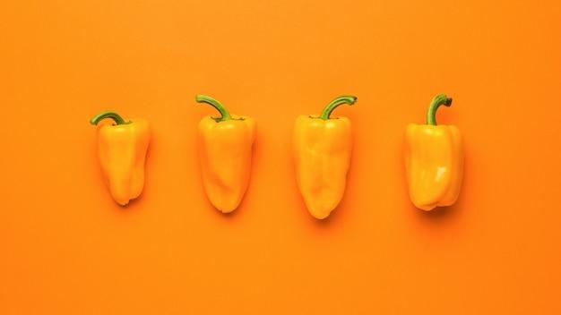 Quatre poivrons oranges mûrs sur fond orange. la nourriture végétarienne.
