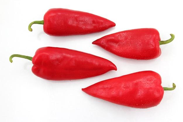 Quatre poivrons rouges vifs sur fond blanc