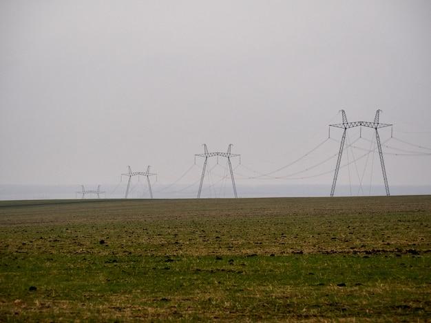 Quatre pylônes électriques prend en charge dans un champ brumeux