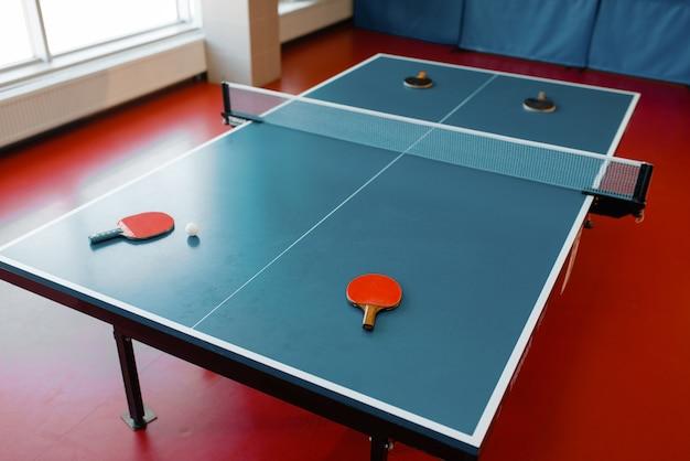 Quatre raquettes de ping-pong sur table de jeu avec filet, personne, vue de dessus. club de tennis de table, concept tennis, symbole ping-pong