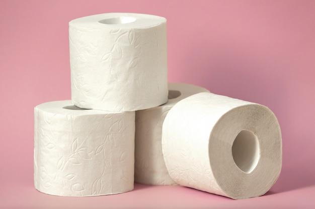 Quatre rouleaux de papier toilette blanc se tiennent sur un fond rose