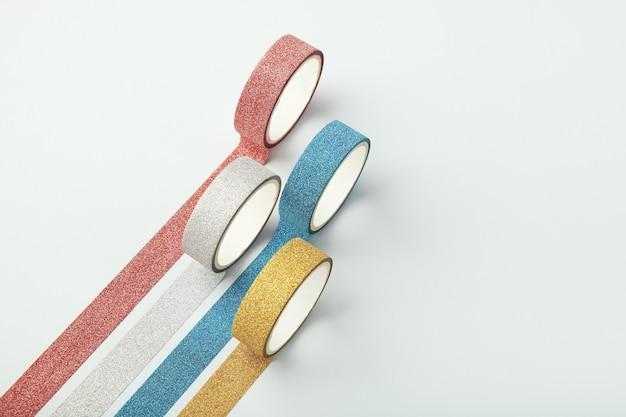Quatre rouleaux de ruban scintillant et de bandes parallèles