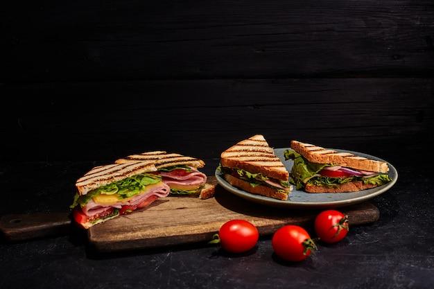 Quatre sandwichs dans l'assiette. fond sombre.