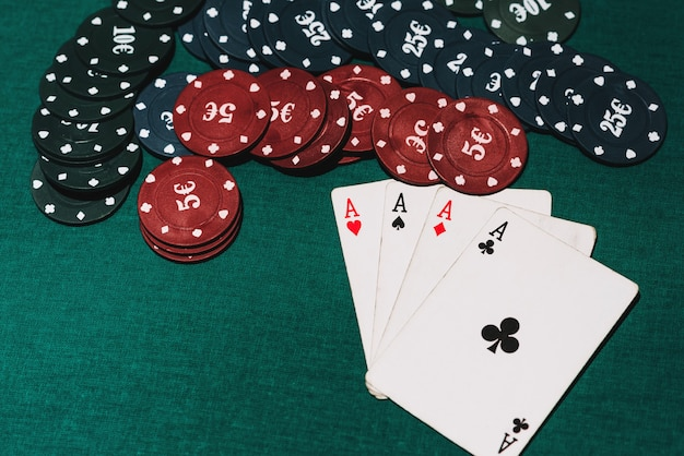 Quatre d'une sorte d'as et de jetons sur la table de poker verte