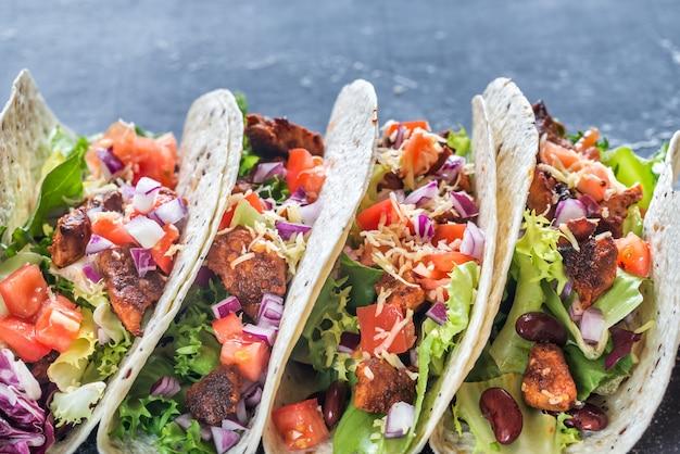 Quatre tacos mexicains sur une surface noire