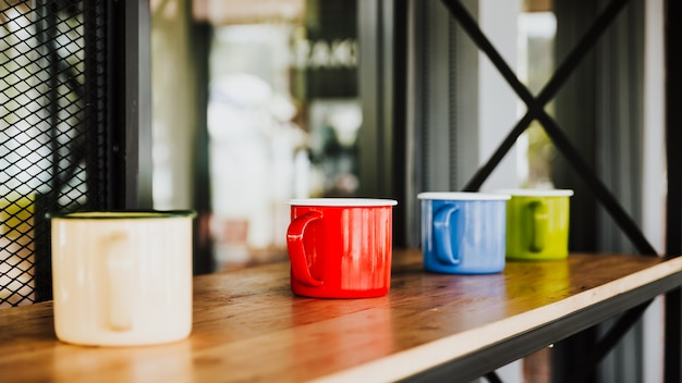 Quatre tasses à café colorées sur un plancher en bois dans un café de luxe.