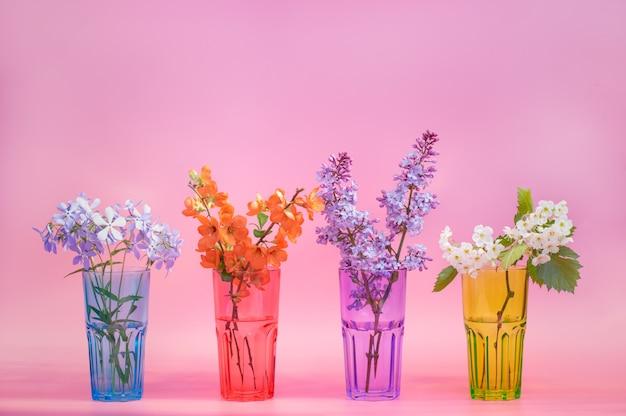 Quatre tasses en verre identiques: rouge, vert, bleu, violet. fleurs de printemps sur fond rose. fermer