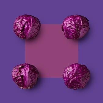 Quatre têtes de chou rouge cru présentées aux angles d'un carré violet sur fond violet. de la série de choux de couleur