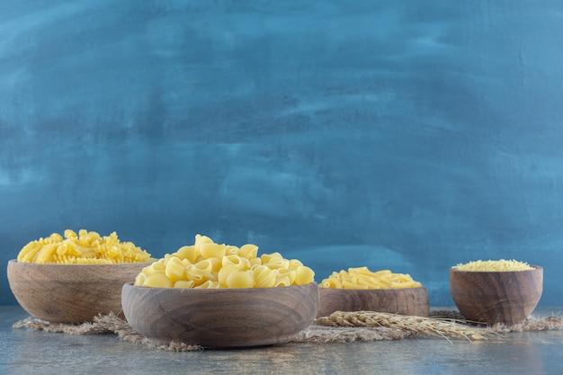 Quatre types de pâtes dans des bols, sur la surface en marbre.