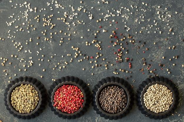 Quatre variations de grains de poivre sur une table en pierre sombre